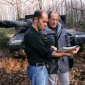 Robert Stone and NPR reporter John Ydstie (as himself) prepare to shoot a scene in front of an M1 tank