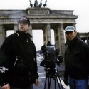 Camerman Matthias Haedecke and director Robert Stone prepare scene at Brandenburg Gate, Berlin